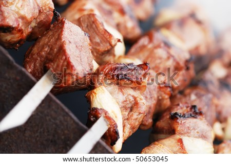 Closeup of meat cooking on a skewer - stock photo