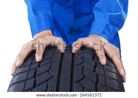 Closeup of mechanic hands holding a textured black tire, isolated on white background - stock photo