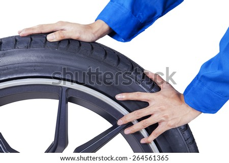 Closeup of mechanic hands pushing a black tire in studio, isolated on white background - stock photo