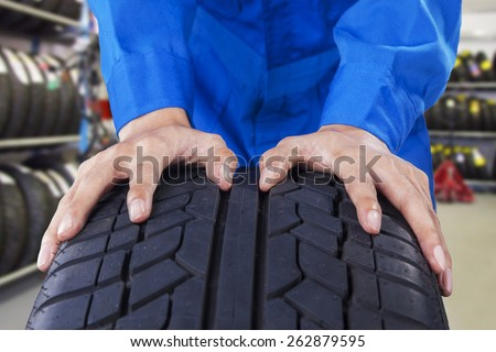 Closeup of mechanic hands with blue uniform pushing a black tire in the workshop - stock photo