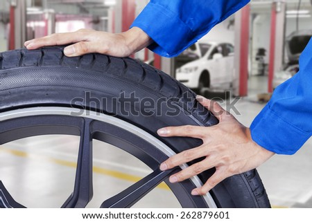 Closeup of mechanic with work wear pushing a black tire at workshop - stock photo
