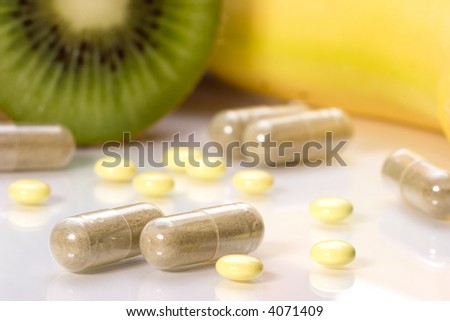 Closeup of medial pills in focus and fruits in background out of focus. Shallow DOF. Image suited for health topics about choice between medicine and healthy food - stock photo
