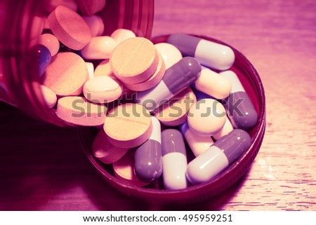 Closeup of medical capsule or pill or drug on wooden background. A lot of colorful medication and pills. - Vintage and Dark tone.
