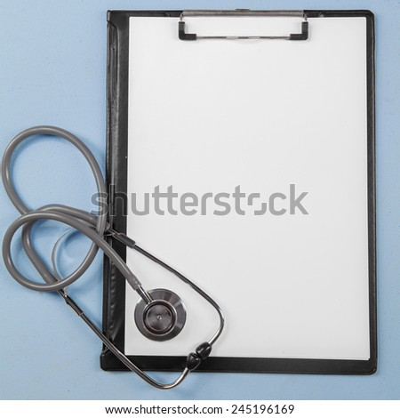 Closeup of medical clipboard with empty paper and stethoscope on the table - stock photo