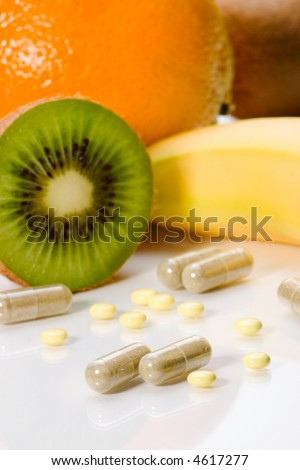 Closeup of medical pills and fruits in background. Shallow DOF. Image suited for health topics about choice between medicine and healthy food - stock photo