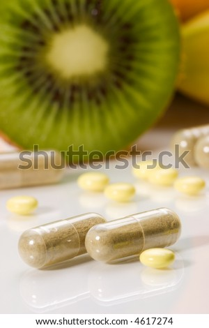 Closeup of medical pills in focus and fruits in background out of focus. Shallow DOF. Image suited for health topics about choice between medicine and healthy food - stock photo