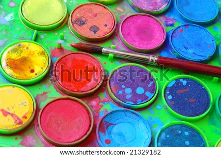 Closeup of messy, used water-color paint box and paint brush. - stock photo
