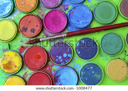 Closeup of messy, used water-color paint-box and paint brush. - stock photo