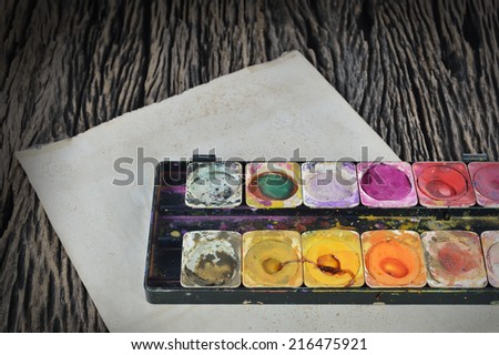 Closeup of messy, used water color paint box on dirty paper - stock photo