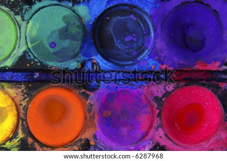 Closeup of messy, used water-color paint-box with black background. - stock photo