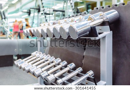 Closeup of metal dumbbells ready to use in a fitness center with sporty people defocused in the background. Weight training equipment concept. - stock photo
