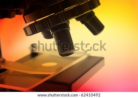 Closeup of microscope on color background - stock photo