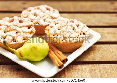 Closeup of mini pies on a plate decorated with cinnamon and a pear  (shallow dof) - stock photo