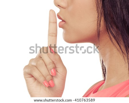Closeup of mixed race woman girl with finger on lips showing hand quiet silence sign gesture isolated on white. - stock photo
