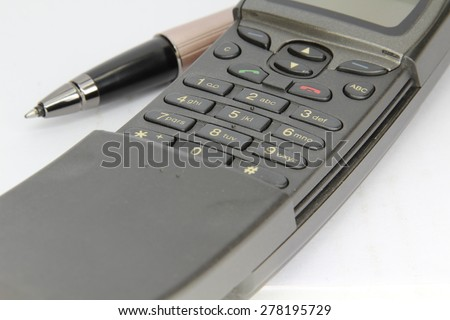 Closeup of mobile phone keypad and pen isolated on white. - stock photo