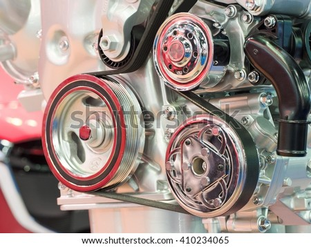Closeup of modern automobile motor car engine part focus on pulley with belt. - stock photo