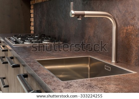 Closeup of modern designer chrome water tap over stainless steel kitchen sink. - stock photo