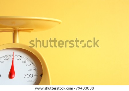 Closeup of modern kitchen scale on yellow background with copy space - stock photo
