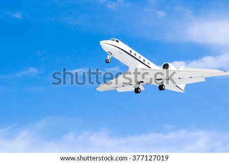 Closeup Of Modern White Minimalist North American Passenger Jet Airplane Flying Against Deep Blue Sky Background Coming In For Landing