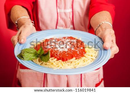 Closeup of mom's hands holding a plate of homemade spaghetti marinara. - stock photo