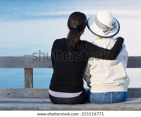 Closeup of mother and mature daughter siting on wooden bench while looking at the lake - stock photo