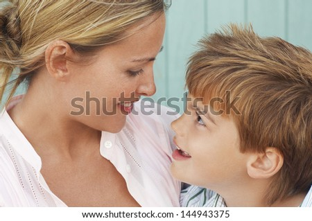 Closeup of mother and son lovingly looking at each other - stock photo
