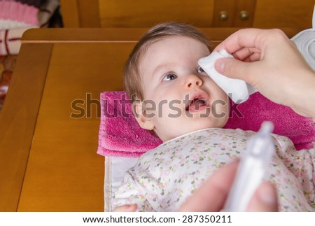 Closeup of mother hands cleaning eyes of baby with physiological serum in a cotton - stock photo