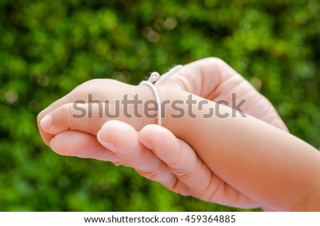 Closeup of mother hands holding tiny baby hands on nature background.