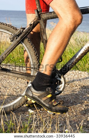 Closeup of mountain bike on dirt track with beach in the background. - stock photo