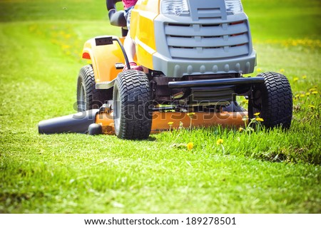 Closeup of mower cutting the grass  - stock photo