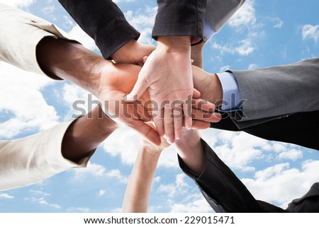 Closeup of multiethnic business people's hands on top of each other symbolizing unity against sky - stock photo