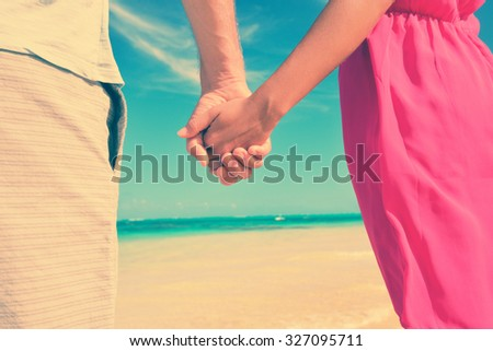 Closeup of multiethnic couple holding hands on shore. Loving young tourists are standing at beach. They are spending leisure time together. - stock photo