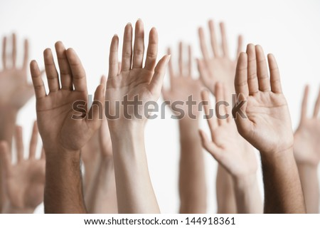 Closeup of multiethnic men and women raising hands against white background - stock photo