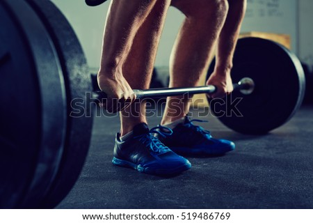 Closeup of muscular man doing deadlift exercise at gym - fitness, healthy lifestyle concept