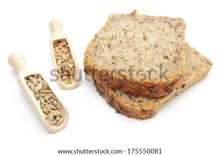 Closeup of natural rye and wheat grain on wooden spoons and pieces of bread. Isolated on white background
