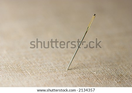 Closeup of needle on linen cloth background. Shallow focus depth on needle.