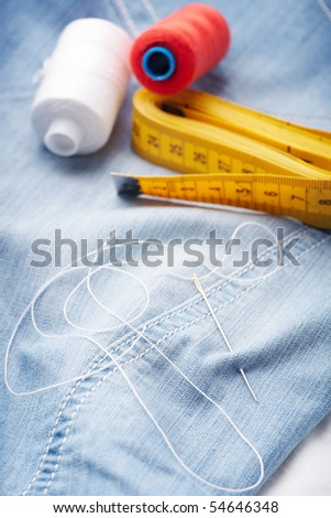 Closeup of needle with thread and ruler (sartorial meter) on jeans material. - stock photo