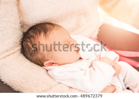 Closeup of newborn baby girl in mother's arms