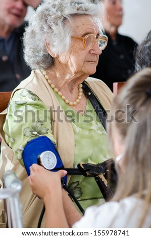 Closeup of nurse checking senior woman blood pressure - stock photo