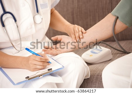 Closeup of nurse measuring blood pressure and checking heartbeat on senior woman's wrist.? - stock photo