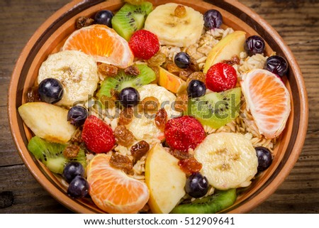 Closeup of oatmeal in bowl with fruits and raisins on old wooden table
