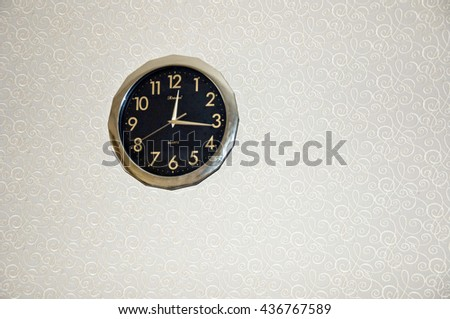 Closeup of oen big round shape old fashioned clock black and gilden color hanging on beige wall indoor with no people, copy space - stock photo