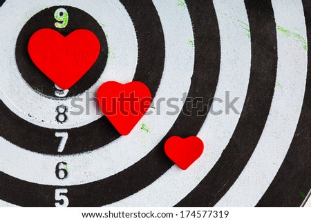 Closeup of old black and white target with red hearts symbols bullseye as love background. Valentines day.