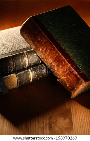 Closeup of old books on nice wooden background under beam of light - stock photo