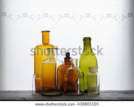 Closeup of old colorful empty glass bottles at windowsill against daylight - stock photo