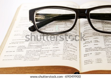 closeup of old dictionary and black glasses - stock photo