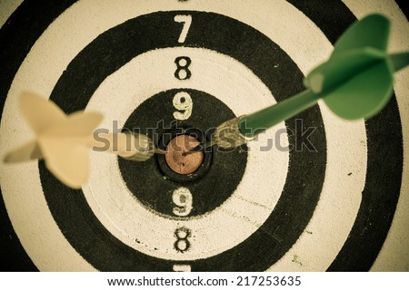 Closeup of old dirty black and white target with two darts as sport background. Skeet trap shooting. - stock photo