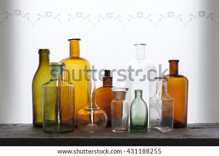Closeup of old empty colorful glass bottles at windowsill against daylight  - stock photo