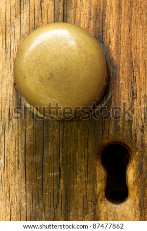 Closeup of old fashioned door knob on wooden door and keyhole. - stock photo