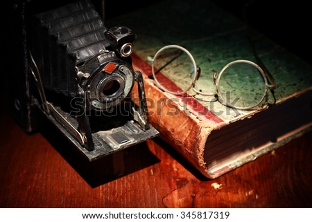 Closeup of old film camera near book on nice wooden background - stock photo